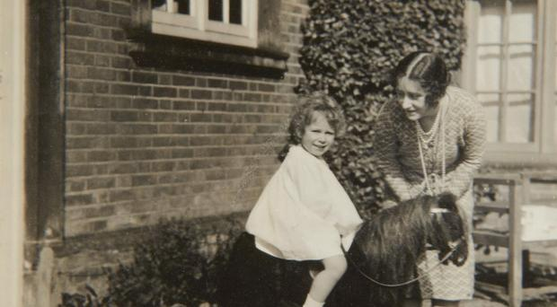 Previously unpublished family photograph issued by the Royal Collection of Queen Elizabeth II with a toy horse in front of Naseby Hall 1928. The pictures are to be seen by the public for the first time to coincide with a book being released this week to mark the birth of Prince George contains new pictures which show the future Queen between the ages of two and four