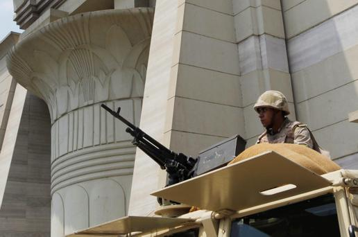 Egyptian Army soldier takes his position on top of an armored vehicle as he guards in front of the Supreme Constitutional court in Cairo