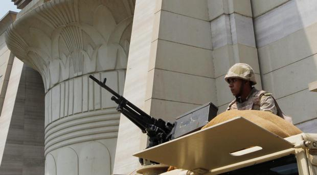 An Egyptian Army soldier takes his position on top of an armored vehicle as he guards in front of the Supreme Constitutional court in Cairo, Egypt, Monday, Aug. 19, 2013. Egypts military leader vows that the army will not tolerate further political violence after nationwide clashes leave hundreds dead. (AP Photo/Amr Nabil)