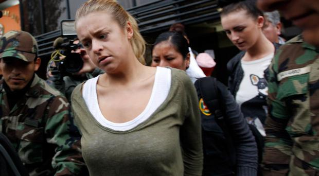 Police escort Michaella McCollum Connolly (right) and Melissa Reid (front) in handcuffs as they are moved from the National Police anti-drug headquarters to a court to be formally charged for drug trafficking in Lima, Peru, Tuesday, Aug. 20, 2013