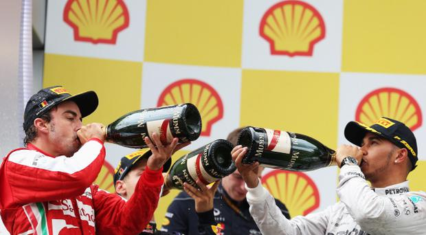 Race winner Sebastian Vettel (C) of Germany and Infiniti Red Bull Racing celebrates alongside second placed Fernando Alonso (left) of Spain and Ferrari and third placed Lewis Hamilton (right) of Great Britain and Mercedes GP on the podium following the Belgian Grand Prix at Circuit de Spa-Francorchamps on August 25, 2013 in Spa, Belgium. (Photo by Mark Thompson/Getty Images)