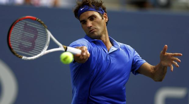 Roger Federer, of Switzerland, returns a shot against Carlos Berlocq, of Argentina, during the second round of the 2013 U.S. Open tennis tournament, Thursday, Aug. 29, 2013, in New York. (AP Photo/Kathy Willens)