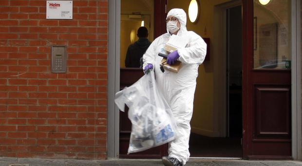 A forensic scientist examines the scene where a woman's body was found in Hill Street in Belfast's Cathedral Quarter