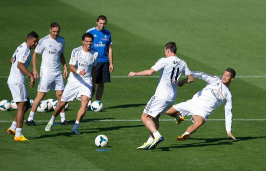 MADRID, SPAIN - SEPTEMBER 13: Real Madrid's new signing Gareth Bale (#11) is tackled by Cristiano Ronaldo while teammates Jese Rodriguez (L), Karim Benzema (2.L), Pepe and assistant coach Zinedine Zidane look on during a team training session on September 13, 2013 in Madrid, Spain. (Photo by Denis Doyle/Getty Images)