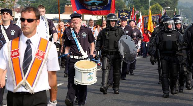 PSNI in riot gear escort an Orange Order feeder parade past the Ardoyne shops in Belfast as tensions were high on the 12th of July.