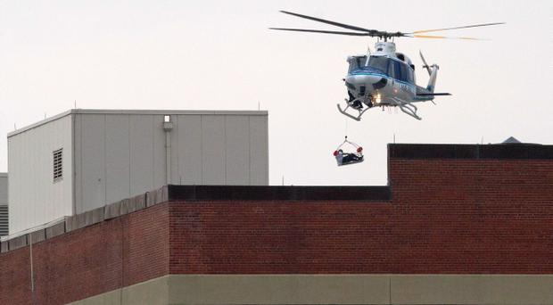A man is airlifted from the top of a building inside the Washington Navy Yard after a gunman was reported at the Navy Yard in Washington, on Monday, Sept. 16, 2013