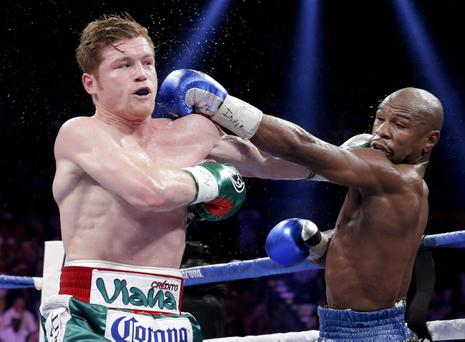 Canelo Alvarez exchanges punches with Floyd Mayweather Jr. in the fifth round during a 152-pound title fight, Saturday, Sept. 14, 2013, in Las Vegas. (AP Photo/Eric Jamison)
