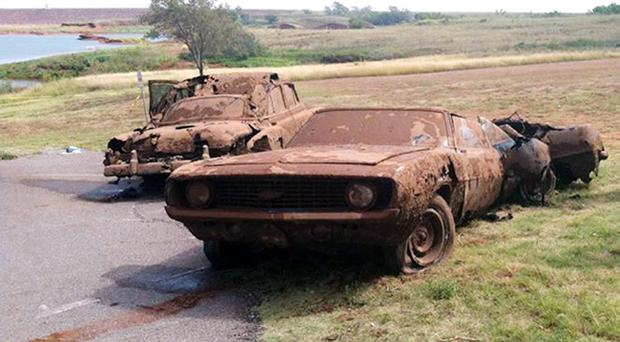 This Sept. 17, 2013, photo shows two cars recovered from Foss Lake, Okla. The Oklahoma State Medical Examiners Office says authorities have recovered skeletal remains of multiple bodies in the Oklahoma lake where the two decades-old cars were pulled from the water by a dive team. (AP Photo/Daily Elk Citian, Laura Eastes)