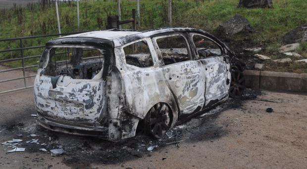 The burnt out car on the Glenside Road outside Belfast after a woman was dragged from her car in west Belfast by three men who hijacked the vehicle and then torched it. Pic Colm Lenaghan/Pacemaker Press