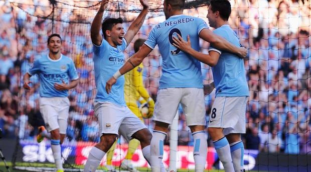 Sergio Aguero of Manchester City (L) celebrates with Alvaro Negredo (9) and Samir Nasri (8) as he scores their third goal during the Barclays Premier League match between Manchester City and Manchester United at the Etihad Stadium on September 22, 2013 in Manchester, England