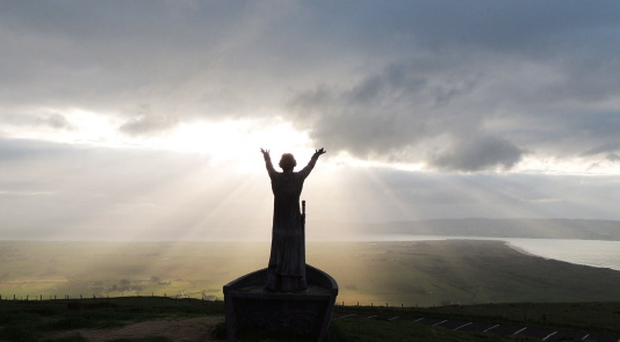 St Colmcille on top of Binevenagh as he beckons to the sun near the end of a beautiful day. Jennifer McClelland, Age 61.
