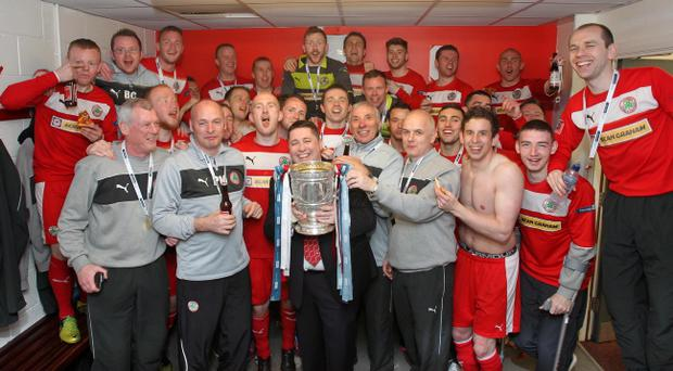 Cliftonville chairman Gerard Lawlor holds the Gibson Cup as the celebrations begin after the Reds clinched the Irish League