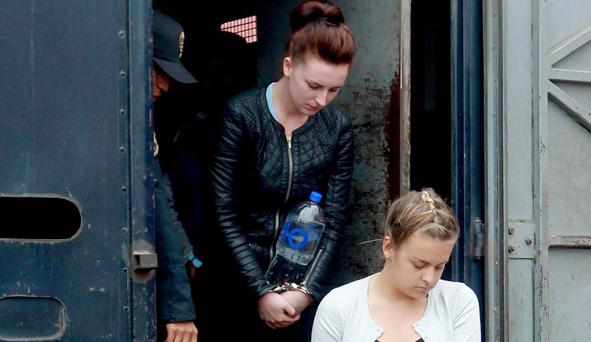 Police escort Melissa Reid, front, and Michaella McCollum Connolly, formally charged for drug trafficking outside a court in Lima, Peru