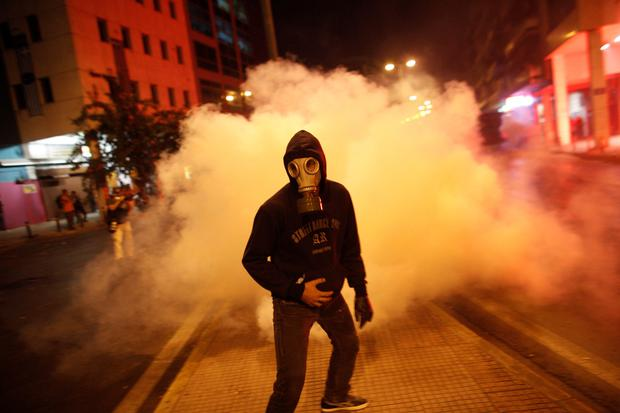 A protester wearing a gas mask leaves after trying to throw back a tear gas canister to riot police during a protest against far-right Golden Dawn party, in Athens, Sept. 25, 2013.