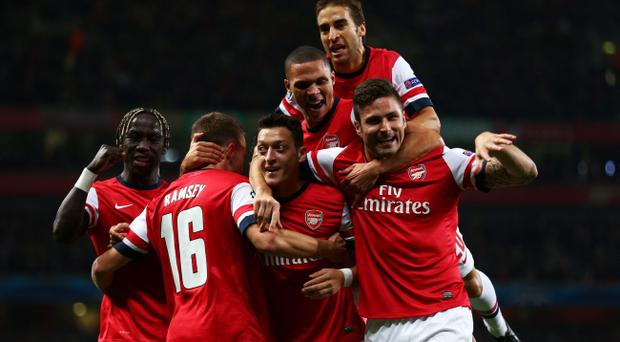 Mesut Oezil (C)of Arsenal is congratulated by teammates after scoring the opening goal during UEFA Champions League Group F match between Arsenal FC and SSC Napoli at Emirates Stadium on October 1, 2013 in London, England. (Photo by Paul Gilham/Getty Images)