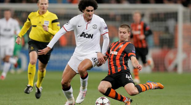 Manchester United's Marouane Fellaini, left, and Shaktar Donetsk's Yaroslav Rakitskiy battle for the ball during their Champions League Group A soccer match at Donbass Arena Stadium in Donetsk, Ukraine, Wednesday, Oct. 2, 2013. (AP Photo/Efrem Lukatsky)