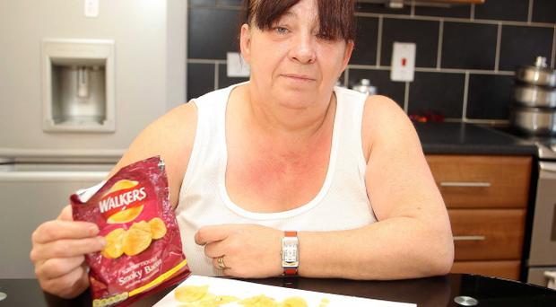 Mary McCormick pictured at her home in north Belfast with a packet of Smokey Bacon crisps