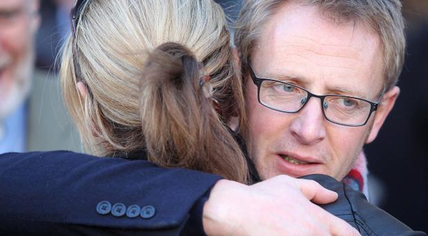 Alan McBride, who lost his wife and father-in-law, is comforted outside West Kirk Presbyterian Church where the service took place with wreath laying in the Shankill Remembrance Garden and at the site of bomb attack