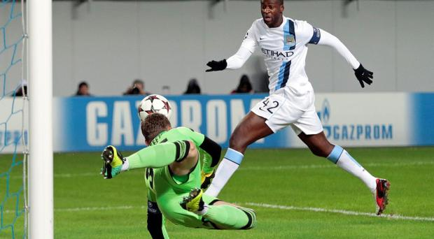 Manchester City's Yaya Toure, right, closes in on the ball as Moscow goalkeeper Igor Akinfeev dives during the UEFA Champions League group D soccer match between CSKA Moscow and Manchester City, at Arena Khimki stadium outside Moscow, Russia, on Wednesday, Oct. 23, 2013. (AP Photo/Ivan Sekretarev)