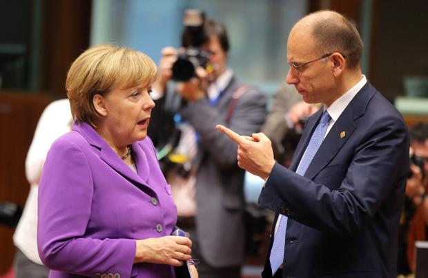 Italian Prime Minister Enrico Letta, right, gestures while speaking with German Chancellor Angela Merkel during a round table meeting at an EU summit on Friday, Oct. 25, 2013. Migration, as well as an upcoming Eastern Partnership summit, will top the agenda in Friday's meeting of EU leaders. (AP Photo/Michel Euler)
