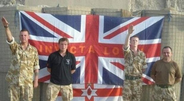Serving British Army soldiers giving the Nazi salute. The Union Flag is inscribed with the words