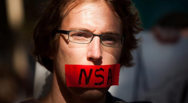 A protester marches with a piece of tape covering his mouth during the Stop Watching Us Rally protesting surveillance by the National Security Agency (NSA), on October 26, 2013, in front of the U.S. Capitol building in Washington, D.C. Photo by Allison Shelley