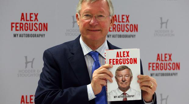 Sir Alex Ferguson holding a copy of his book