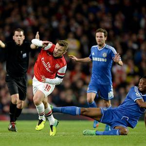 Arsenal's Jack Wilshere (left) and Chelsea's Mikel battle for the ball during the Capital One Cup, Fourth Round match at the Emirates Stadium, London.