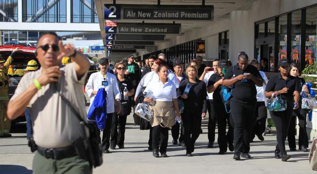 Passengers are directed outside Terminal 2 at Los Angeles International Airport on Friday Nov. 1, 2013, after shots were fired, prompting authorities to evacuate a terminal and stop flights headed for the city from taking off from other airports. (AP Photo/Ringo H.W. Chiu)