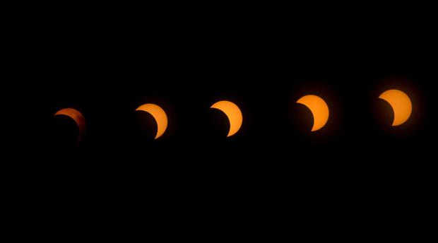This multiple exposure image shows the transition from right to left of a hybrid solar eclipse seen over Lake Oloidien near Naivasha in Kenya Sunday, Nov. 3, 2013. A rare solar eclipse swept across parts of the US, Africa and Europe on Sunday with some areas witnessing a total blackout and others experiencing a partial version. (AP Photo/Ben Curtis)