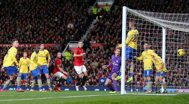 Manchester United's Robin van Persie scores with a header against his former Arsenal teammates at Old Trafford, Manchester.