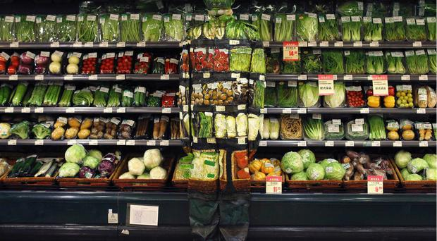 Artist Liu Bolin, also known as the 'Vanishing Artist,' demonstrates an art installation by blending in with vegetables displayed on the shelves at a supermarket in Beijing. REUTERS/China Daily