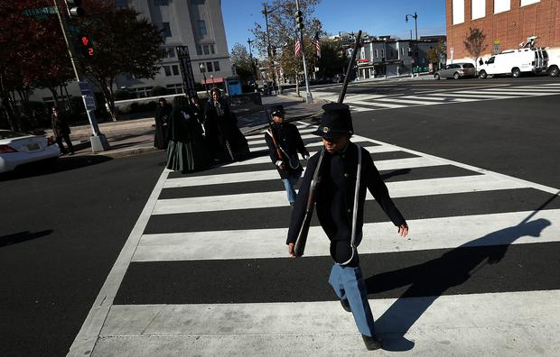 Wyatt Harris (R) and Joshua Terry (2nd R), dressed in Civil War military uniforms, cross the street after taking part in a wreath-laying ceremony commemorating Veterans Day and honoring the Tuskegee Airmen November 11, 2013 in Washington, DC. Photo by Win McNamee