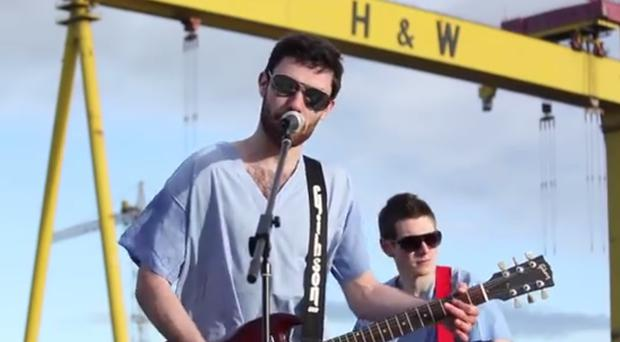 The video sees SWOT emerge from a hospital ward to perform in their scrubs in front of Queen's University's Lanyon Building and in front of the Harland & Wolff cranes at the city's docks.