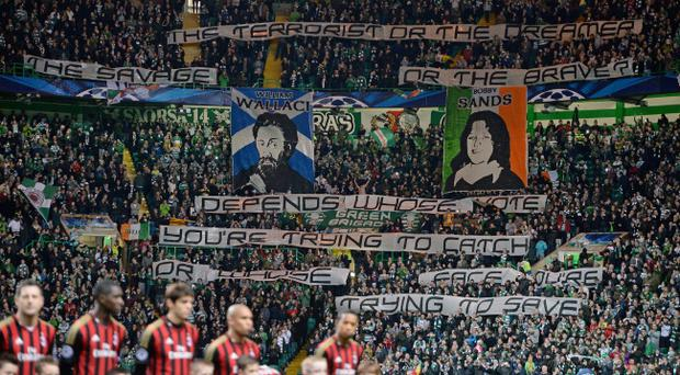 Celtic supporters wave banners during the UEFA Champions League Group H match between Celtic and AC Milan at Celtic Park Stadium last month