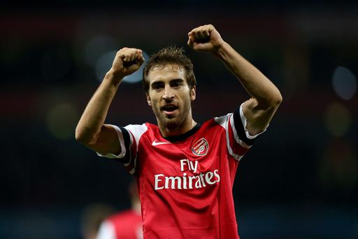 Arsenal's Mathieu Flamini celebrates after his team-mate Jack Wilshere scored his team's second goal during the UEFA Champions League match at the Emirates Stadium, London. Flamini wore short sleeves in contrast to the rest of the Arsenal team