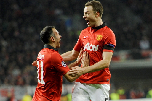 Manchester United's Jonny Evans, right, and Manchester United's Ryan Giggs celebrate their side's third goal during the Champions League group A soccer match between Bayer Leverkusen and Manchester United in Leverkusen, Germany, Wednesday, Nov. 27, 2013. (AP Photo/Martin Meissner)