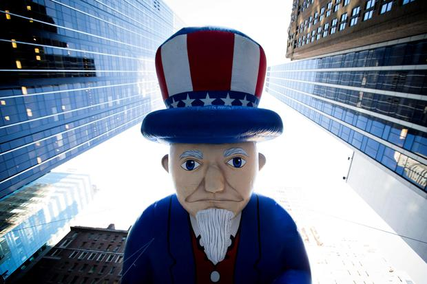 A giant Uncle Sam balloon is marched down 6th Avenue during the 87th Annual Macy's Thanksgiving Day Parade, Thursday, Nov. 28, 2013, in New York. (AP Photo/John Minchillo)