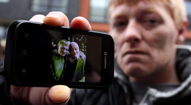 John McGarrigle, 38, holds a mobile phone showing a photo of him with his father also John McGarrigle, 59, who he says was killed in The Clutha Bar helicopter crash, Glasgow