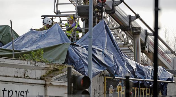 Rescue workers attend the scene at a pub on Stockwell Street where a police helicopter crashed on the banks of the River Clyde November 30, 2013 in Glasgow