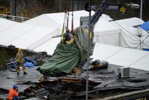 GLASGOW, SCOTLAND - DECEMBER 02: Rescuers lift the police helicopter wreckage from the roof of the The Clutha Pub on December 2, 2013 in Glasgow, Scotland. A ninth body has been recovered in the wreckage of Glasgow's Clutha pub which was destroyed when a police helicopter crashed on to the roof of it on Friday night. (Photo by Jeff J Mitchell/Getty Images)