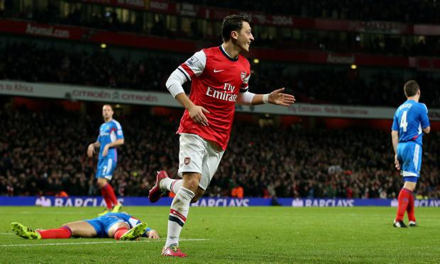 Arsenal's Mesut Ozil celebrates celebrates scoring his teams second goal during the Barclays Premier League match at the Emirates Stadium, London