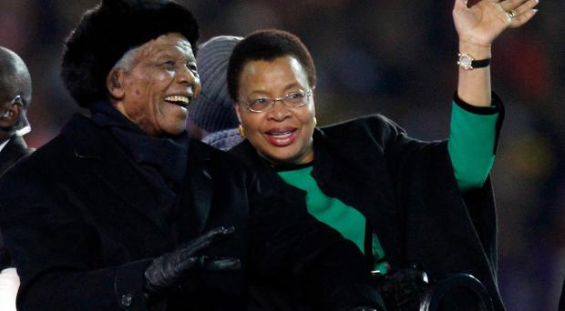 FILE - In this July 11, 2010 file photo, former South African President Nelson Mandela, left, sits next to his wife, Graca Machel, as they are driven across the field ahead of the World Cup final soccer match between the Netherlands and Spain at Soccer City in Johannesburg, South Africa.