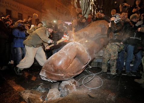 Ukrainian protesters smash a statue of Vladimir Lenin with a sledgehammer, in central Kiev, Ukraine, Sunday, Dec. 8, 2013. Anti-government protesters have toppled the statue of Bolshevik leader Vladimir Lenin in central Kiev amid huge protests gripping Ukraine. (AP Photo/Efrem Lukatsky)