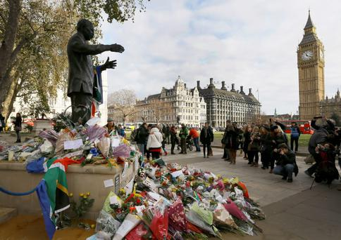 People gather to look at flowers and tributes left at the statue of Nelson Mandela in Parliament Square, London, Sunday, Dec. 8, 2013. Mandela died Thursday after a long illness, he was 95. Big Ben's clock tower at right. (AP Photo/Kirsty Wigglesworth)