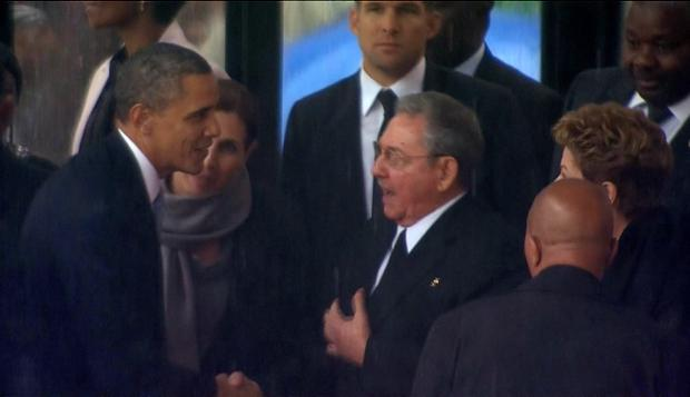 In this image from TV, US President Barack Obama shakes hands with Cuban President Raul Castro at the FNB Stadium in Soweto, South Africa, in the rain for a memorial service for former South African President Nelson Mandela, Tuesday Dec. 10, 2013. The handshake between the leaders of the two Cold War enemies came during a ceremony that's focused on Mandela's legacy of reconciliation. Hundreds of foreign dignitaries and world heads of states gather Tuesday with thousands of South African people to celebrate the life, and mark the death, of Nelson Mandela who has became a global symbol of reconciliation. (AP Photo/SABC Pool)