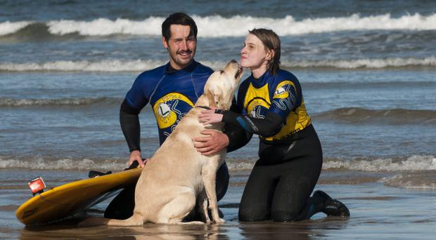 New experience: Gide dog Ushi and Tori Tennant who is learning to surf, on Benone Beach