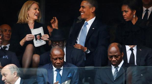 President Barack Obama jokes with Danish prime minister, Helle Thorning-Schmidt, left, as first lady Michelle Obama looks on during the memorial service for former South African president Nelson Mandela at the FNB Stadium in Soweto, near Johannesburg, South Africa, Tuesday Dec. 10, 2013. (AP Photo/Matt Dunham)