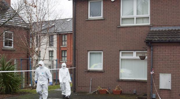 Police officers pictured at the property in the Ravenhill area of Belfast where two dead bodies were discovered yesterday afternoon