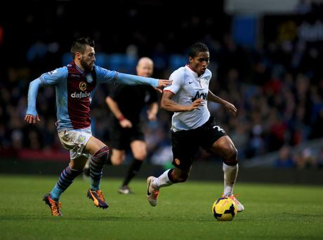 Luis Antonio Valencia of Manchester United is chased by Antonio Luna of Aston Villa during the Barclays Premier League match between Aston Villa and Manchester United at Villa Park on December 15, 2013 in Birmingham, England.